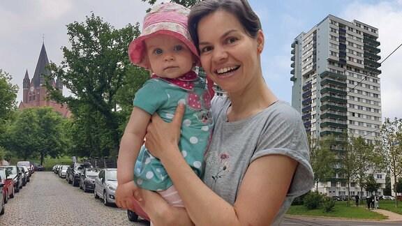 Frau mit Kind neben einer Kirche und einem Hochhaus.