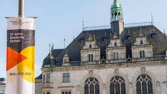 Vor dem Stadthaus von Halle (Saale) hängt ein Banner, das auf Feierlichkeiten zum 31. Jahrestag der deutschen Einheit hinweist.