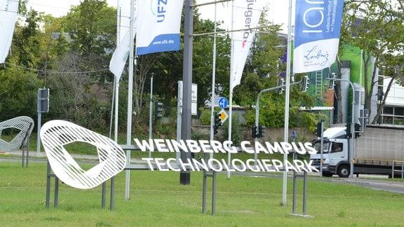 Blick auf einen Schriftzug, der in die Mitte einer begrünten Verkehrsinsel gesetzt wurde. Darauf steht: Technologiepark Weinbergcampus