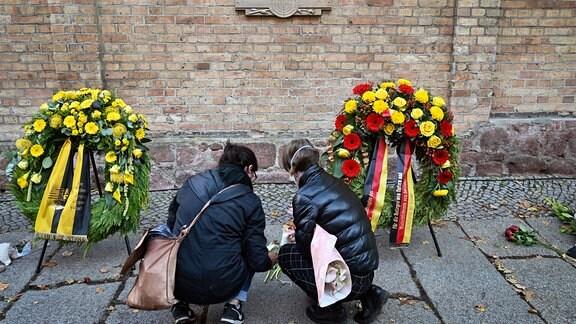 Menschen gedenken vor der Synagoge in Halle/Saale den Opfern des Halle-Attentats.