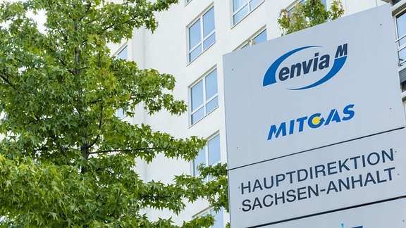 Vor einem Firmensitz in Halle ist das Logo von Envia M Mitgas zu sehen, daneben steht ein Baum.