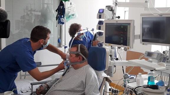 Zwei Männer kümmern sich um einen Patienten auf der Intensivstation.