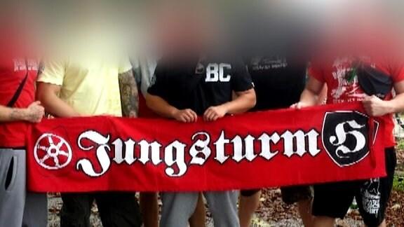 eine Gruppe von sechs Menschen hält ein rotes Banner mit Aufschrift Jungsturm, einem Radsymbol und einem Wappen mit dem Buchstaben H, Köpfe unkenntlich gemacht
