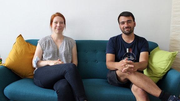 Eine Frau und ein Mann sitzen auf einem Sofa und schauen lächelnd zur Kamera.