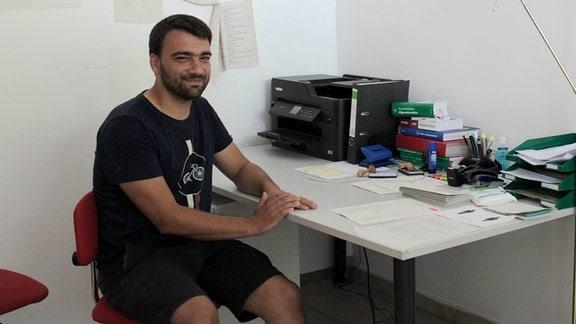 Ein Mann sitzt an einem Schreibtisch und schaut lächelnd zur Kamera.