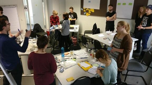 Studenten des Studiengangs Multimedia und Autorschaft stehen in einem Seminarraum der Martin-Luther-Universität in Halle.