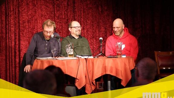 Drei Männer sitzen an einem Tisch auf einer Bühne