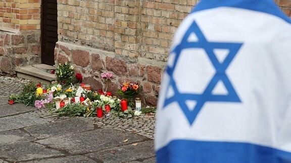 Ein Mann mit einer Israel-Flagge steht vor der Synagoge, wo Blumen und Kerzen stehen und liegen