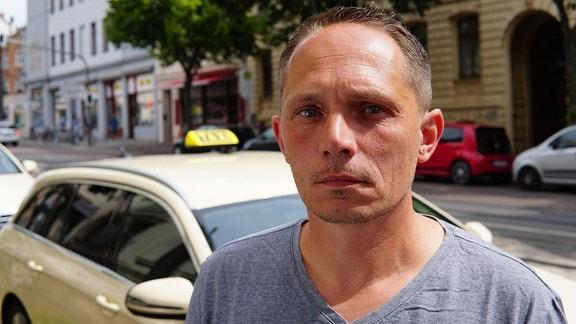 Ein Mann steht vor einem Taxi und blickt in die Kamera.