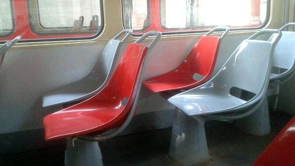 Ein Bilick in den Innenraum der Tatrabahn offenbart die einfache und bewährte Doppelbestuhlung in rot und grau