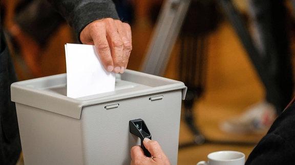 Eine Person wirft einen Wahlzettel in eine Wahlurne.