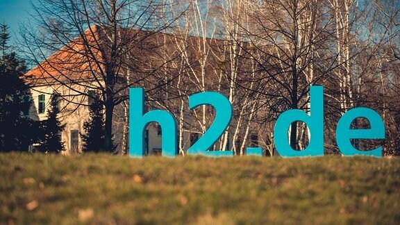 Hochschule Magdeburg-Stendal. Das Logo h2.de auf einer Wiese.