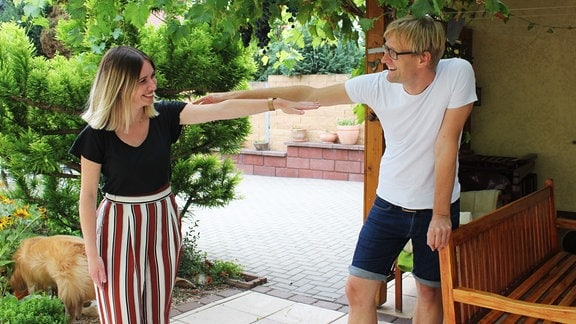Ein Mann und eine junge Frau gucken sich an und strecken jeweils einen Arm zueinander aus.