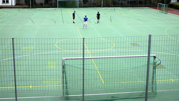 Sportplatz einer Schule in Zeiten von Corona, mit drei Jungen, die Fussball spielen.