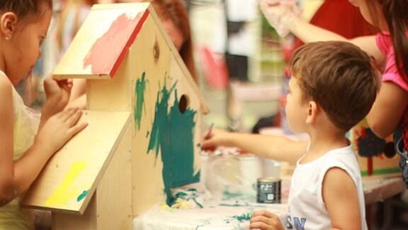Zwei Mädchen und ein Junge malen im Kindergarten ein Vogelhaus mit grüner Farbe an.