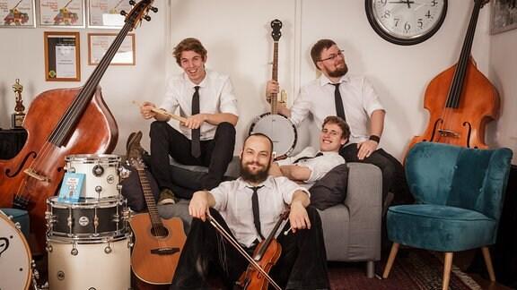 Mehrere Männer sitzen mit Instrumenten in einem Wohnzimmer.