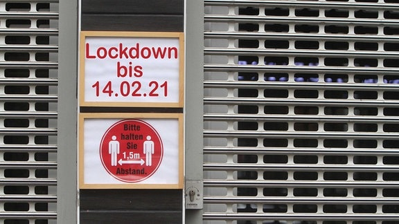 Symbolbild zum Thema Verschärfung der Maßnahmen gegen Corona: Schild mit Aufschrift Lockdown bis zum 14. Februar 2021 an einem mit Rolltor verschlossenen Geschäfts in der Innenstadt von Frankfurt, Hessen.