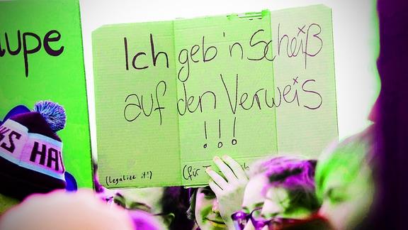 Junge Menschen mit Plakaten in den Händen auf einer Demo.