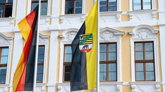 Flaggen von Sachsen-Anhalt und Deutschland vor einem Gebäude.