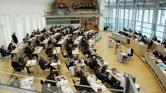 Abgeordnete sitzen im Sitzungssaal des Landtags.