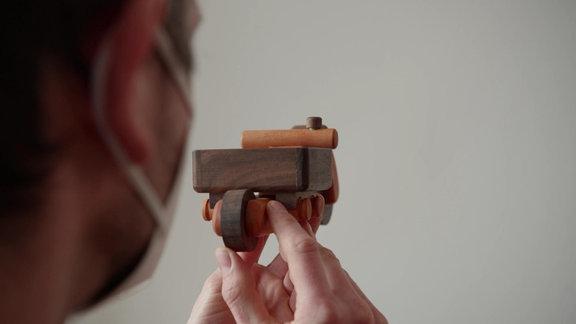Ein Mann hält ein Spielzeugfahrrad aus Holz in den Händen.
