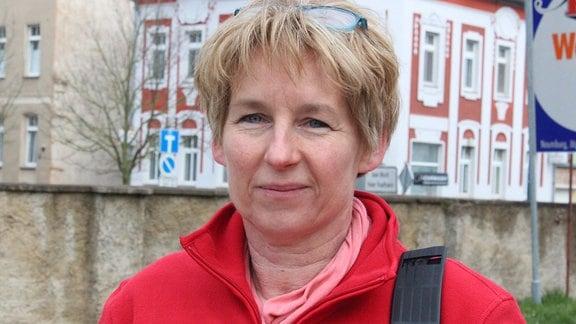 Eine Frau in roter Jacke steht vor einer Mauer und blickt in die Kamera.