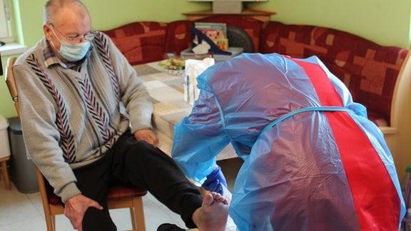 Eine Mitarbeiterin eines ambulanten Pflegedienstes versorgt die Wunde eines älteren Mannes am Fuß.