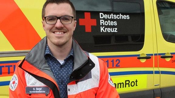 Ein Mann in oranger Warnweste steht vor einem Rettungswagen des Deutschen Roten Kreuzes und lächelt in die Kamera.