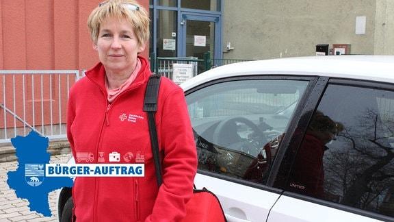 Eine Frau steht in roter Jacke des Deutschen Roten Kreuzes vor einem Dienstwagen und schaut in die Kamera.