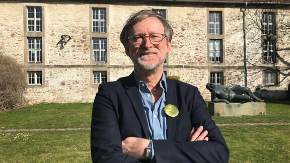Der Rektor der Burg Giebichenstein, Dieter Hofmann, steht mit verschränkten Armen vor einem Gebäude der Kunsthochschule.
