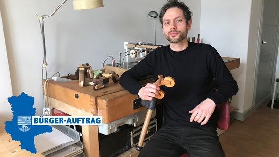 Ein Mann sitzt in einem Atelier und lehnt an einem Tisch. In der Hand hält er ein Holzspielzeug.