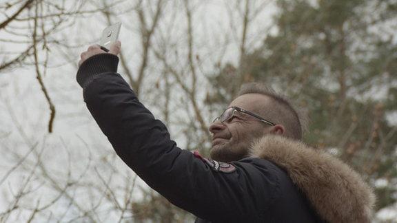 Ein Mann hält sein Handy in die Luft und schaut darauf.