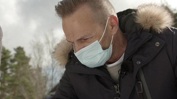 Ein Mann mit Mund-Nasen-Schutz lehnt über einem nicht sichtbaren Bauplan.