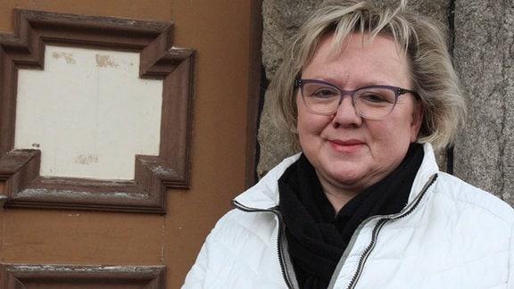 Die Ortsbürgermeisterin von Schierke steht vor der Tür des historischen Rathauses.