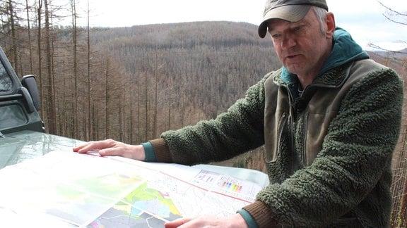 Ein Mann blickt auf eine Karte mit verschieben farbigen Flecken, die auf der Motorhaube eines Autos ausgebreitet ist.