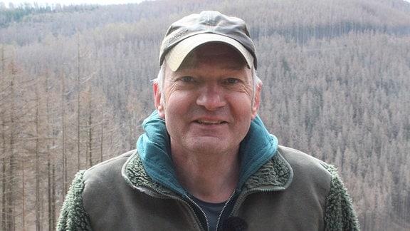 Ein Mann steht vor einer Schneise in einem Wald.