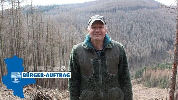 Ein Mann steht vor einer Schneise in einem Wald und lächelt in die Kamera.