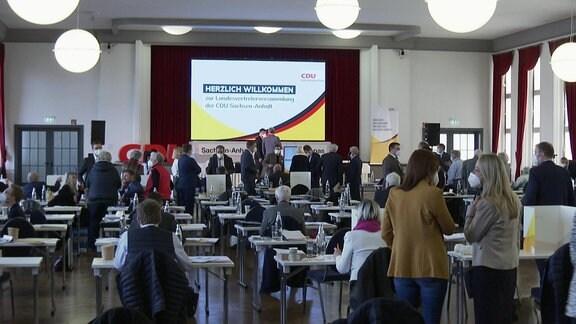 Delegierte sitzen ohne Maske am Platz und stehen mit Maske im Gang am 20. Februar in dem Saal, in dem die CDU Sachsen-Anhalt ihren Listenparteitag abhält