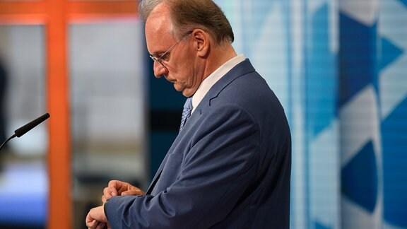 Reiner Haseloff (CDU), Ministerpräsident von Sachsen-Anhalt, schaut am Abend der Landtagswahl auf seine Uhr.