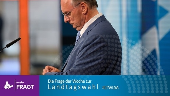 Wahlsieger Reiner Haseloff (CDU) schaut am Abend der Landtagswahl 2021 auf seine Uhr