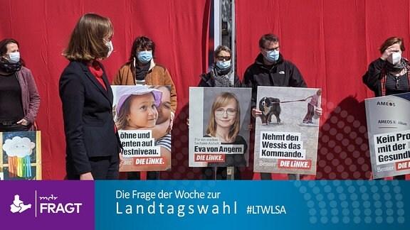 """Linke-Spitzenkandidatin Eva von Angern schaut bei einem Pressetermin auf das Plakat ihrer Partei mit dem Spruch """"Nehmt den Wessis das Kommando"""", darunter ist ein Kind zu sehen, dass an einem Hund zieht"""