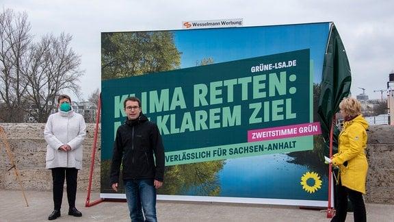Der Landesvorsitzende der Grünen, Sebastian Striegel, steht vor einem Wahlplakat, neben ihm Umweltministerin Claudia Dalbert und Spitzenkandidatin Cornelia Lüddemann.