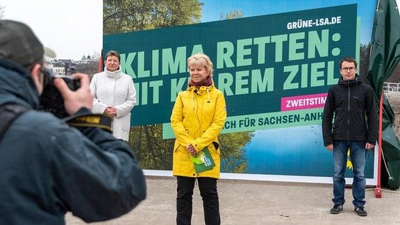 Die Spitzenkandidatin der Grünen, Cornelia Lüddemann, steht vor einem Wahlplakat, neben ihr Umweltministerin Claudia Dalbert und Grünen-Landeschef Sebastian Striegel, links im Bild ein Fotograf.
