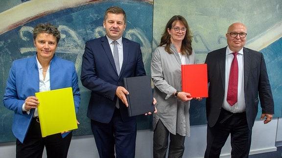 Lydia Hüskens (l-r), Vorsitzende der FDP in Sachsen-Anhalt, Sven Schulze, Vorsitzender der CDU in Sachsen-Anhalt, Juliane Kleemann und Andreas Schmidt, beide Vorsitzende der SPD in Sachsen-Anhalt, zeigen den unterschriebenen Koalitionsvertrag.