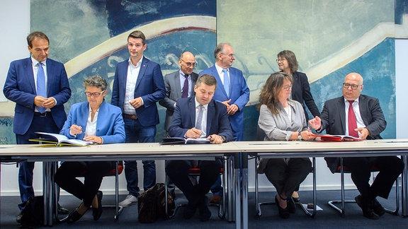 Andreas Silbersack (FDP, l-r), Fraktionsvorsitzender, Lydia Hüskens und Marcus Faber, beide Vorsitzende der FDP in Sachsen-Anhalt, Siegfried Borgwardt (CDU), Fraktionsvorsitzender, Sven Schulze, Vorsitzender der CDU in Sachsen-Anhalt, Reiner Haseloff (CDU), amtierender Ministerpräsident in Sachsen-Anhalt, Juliane Kleemann, Vorsitzende der SPD in Sachsen-Anhalt, Katja Pähle (SPD), Fraktionsvorsitzende und Andreas Schmidt, Vorsitzender der SPD in Sachsen-Anhalt, stehen bzw. sitzen beim Unterschreiben des Koalitionsvertrages am Tisch.