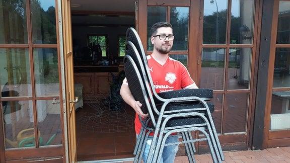 Ein Mann trägt drei gestapelte Stühle