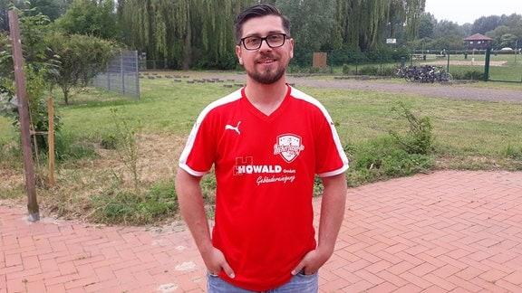 Ein Mann in einem roten T-Shirt steht im Garten