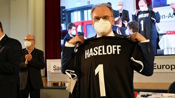 Reiner Haseloff hält nach seiner Wahl zum Spitzenkandidaten ein Trikot mit der Aufschrift -Haseloff 1- in die Kamera.