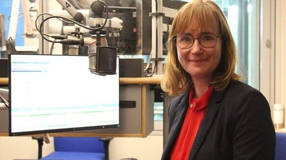 Die Linken-Spitzenkandidatin Eva von Angern sitzt in einem Radiostudio und lächelt in die Kamera.