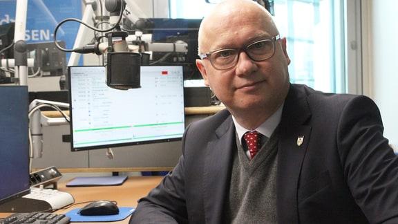 AfD-Spitzenkandidat Oliver Kirchner sitzt in einem Radiostudio und lächelt in die Kamera.